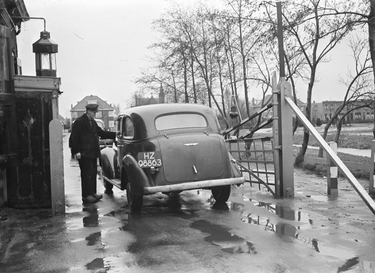 De laatste opening van het tolhek aan de Bodegraafsestraatweg in Gouda door tolgaarder Jan Swager, januari 1948.