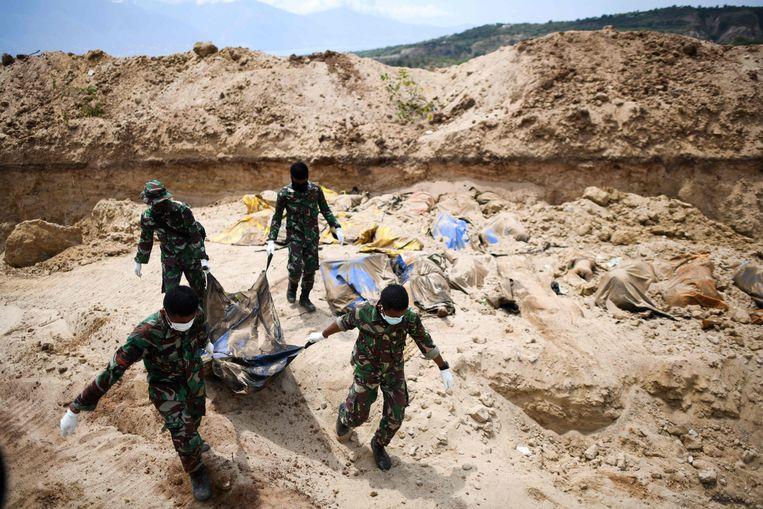 Indonesische soldaten brengen slachtoffers naar een massagraf in Poboya.  Beeld AFP
