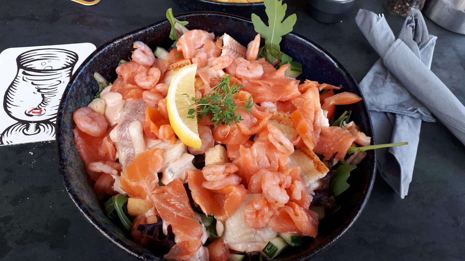 Salade met Noorse garnalen, zalm en paling, geserveerd met stokbrood en boter. Ik bestelde hem als voorgerecht, maar krijg de royale variant (hoofdgerecht), voor 15,95 euro.