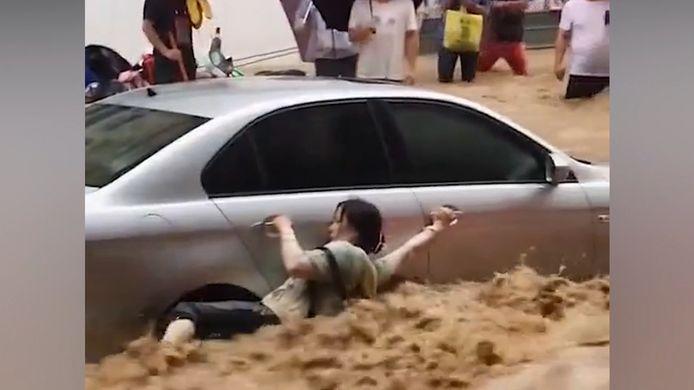 Une femme lutte pour sa vie au milieu des inondations.