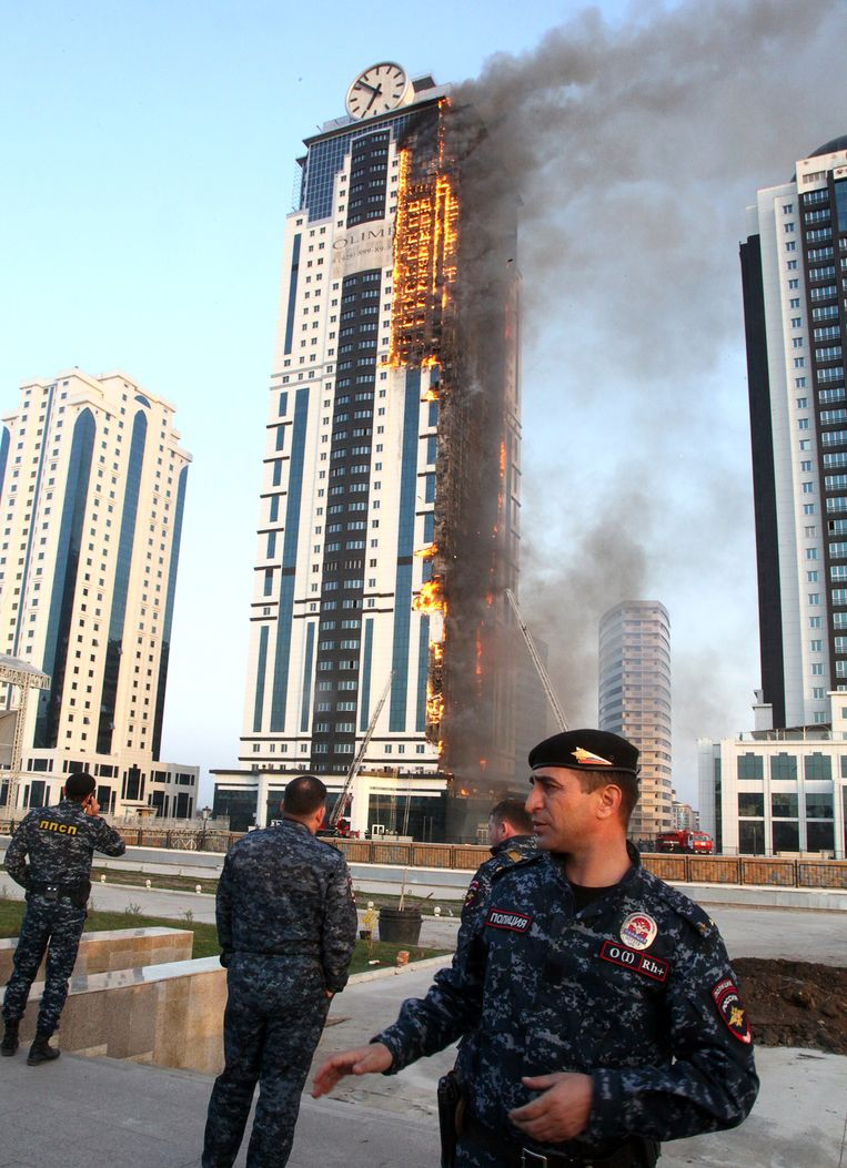 Chechen policemen put cordons round a burning building in central Grozny on April 3, 2013. A fire raged in a skyscraper in the Chechnya capital Grozny on Wednesday, a building which is a centrepiece of a drive by local authorities to promote the city as a glitzy and modern hub. The buildng is uninhabited. AFP PHOTO / ELENA FITKULINA Beeld null