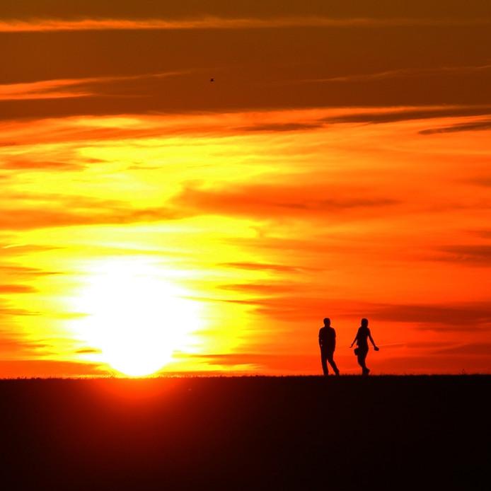 Wandelaars bij zonsondergang op een dijk in Zeeland (lezersfoto).