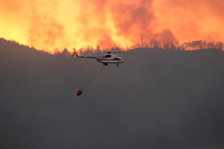 Een brandweerhelikopter probeert de bosbranden in de Turkse stad Marmaris te bedwingen. Beeld EPA