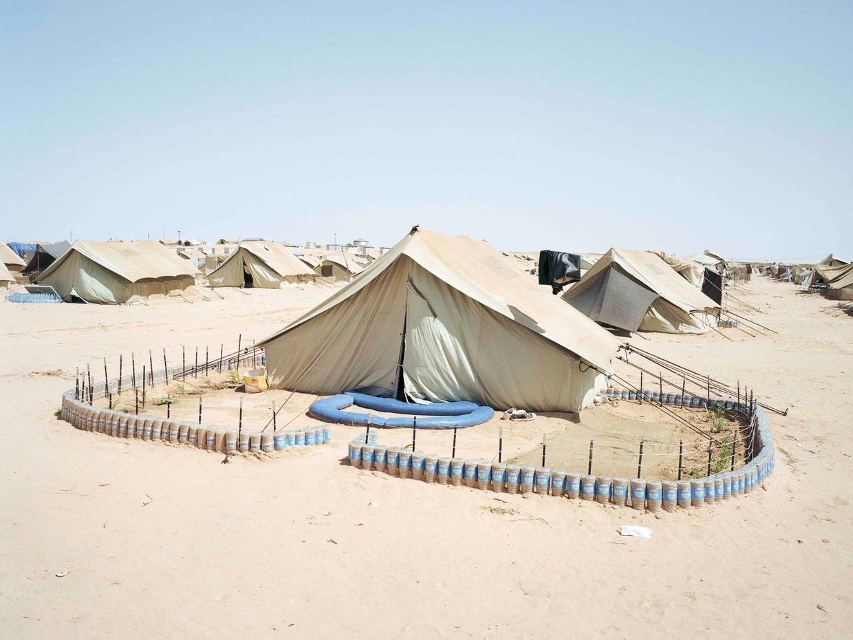 Tuintje met hek van plastic flessen in vluchtenlingenkamp Sousha, Tunesië, tegen de grens met Libië.   Beeld Henk Wildschut