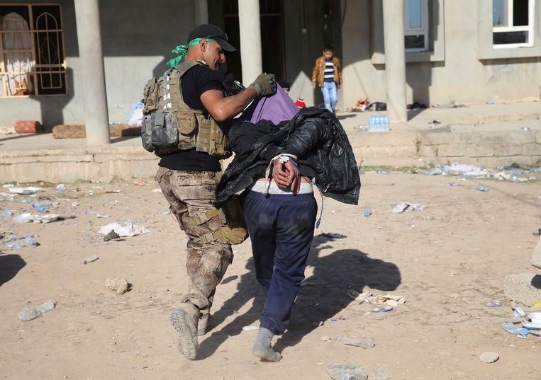 Een Iraakse elitesoldaat brengt een vermoedelijke strijder van Islamitische Staat weg. Beeld AP