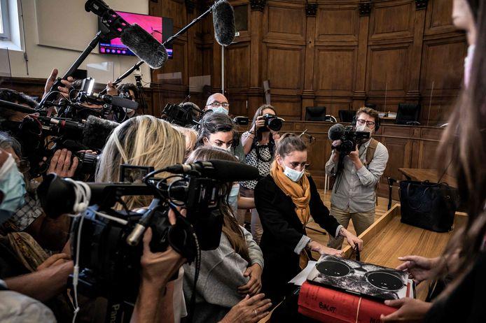 Valérie Bacot, met beige sjaal, wordt omstuwd door cameraploegen in de rechtszaal in Chalon-sur-Saône.