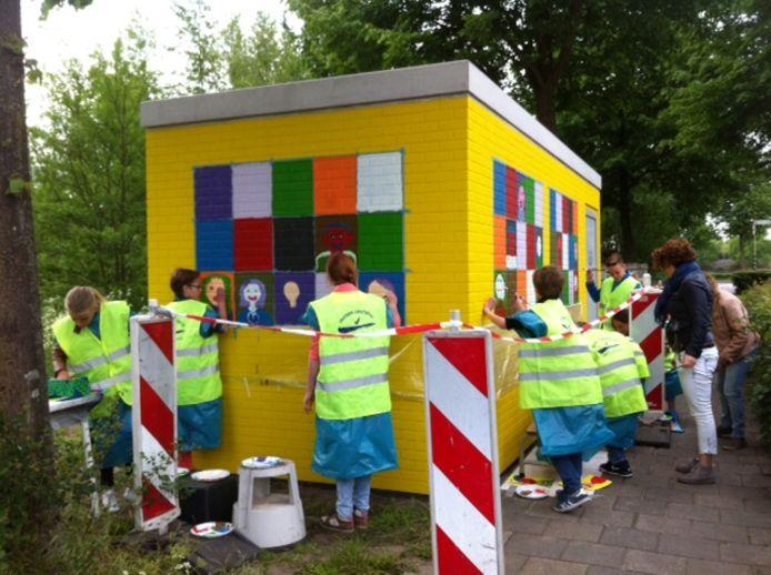 Leerlingen van basisschool Marcoen in Dorst tijdens het schilderen van het zogeheten POP-station van Reggefiber.
