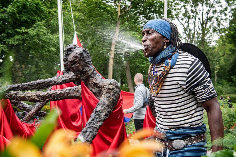 Een Surinaamse Nederlander spuwt bier over het monument in het Oosterpark in Amsterdam na het officiële programma rond Keti Koti op 1 juli 2020.   Beeld Guus Dubbelman / de Volkskrant