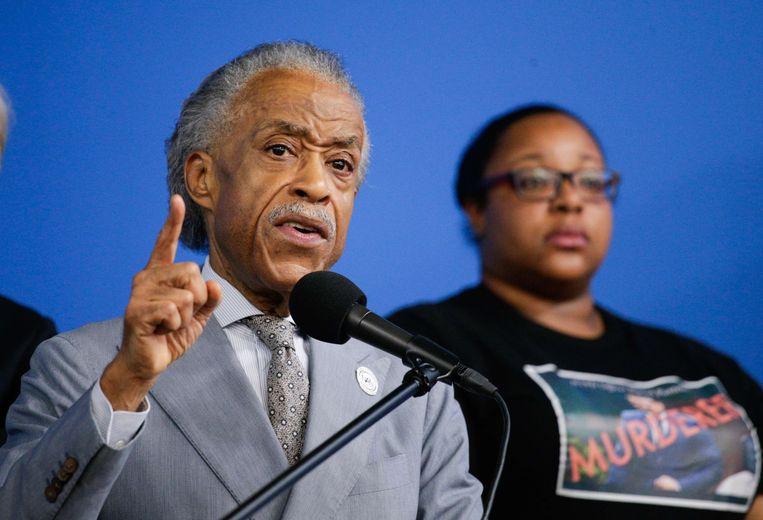 Met Eric Garners dochter aan zijn zijde, juicht de zwarte New Yorkse leider Al Sharpton het besluit toe om de agent de laan uit te sturen. Het tweetal vindt wel dat andere agenten ook bestraft moeten worden.  Beeld AFP