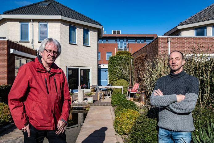 Hendrik Snijders (links) en Dries van Marle in de achtertuin van Van Marle. Het bruinrode kantoorgebouw op de achtergrond wordt een appartementencomplex voor cliënten van Iriszorg.