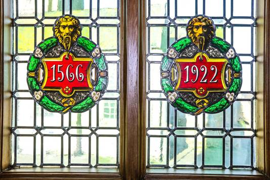 Op glasramen in het gebouw zijn data van de bouw en heropbouw verwerkt.