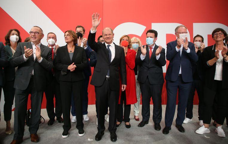 Olaf Scholz en partijgenoten van de SPD vieren de overwinning bij de Duitse parlementsverkiezingen. Beeld Wolfgang Kumm/dpa