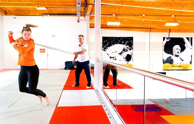 Judoka Sanne van Dijke trekt aan een elastiek tijdens een conditietraining met haar trainer Michael Bazynski in de Ruska-hal op Papendal. Van Dijke werd in 2017 Europees kampioen en aast op een startbewijs voor Tokio in de klasse tot 70 kilo. Nog 102 dagen tot de Spelen. Beeld Klaas Jan van der Weij / de Volkskrant