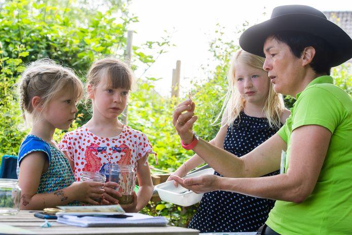 Melang Haarbrink laat aan de kinderen zien wat ze zelf allemaal hebben gevangen in het water.