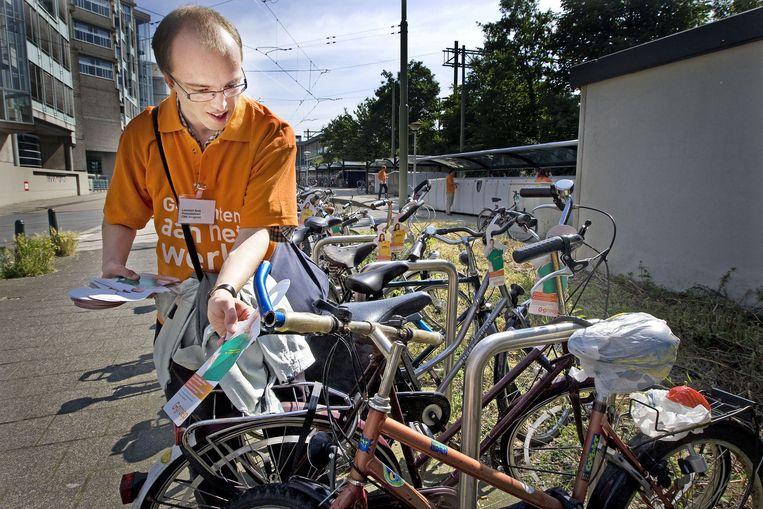 Een wajonger hangt flyers op aan fietsen om actie te voeren voor banen voor jonggehandicapten. Beeld anp