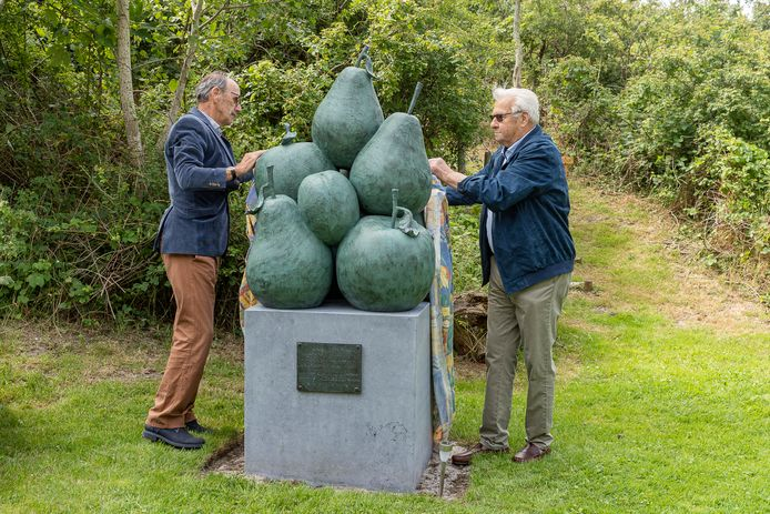 Cor Kooman (links) en Hans Dalebout onthullen het bronzen beeld van Vincent Krans, dat herinnert aan fruitgaardvereniging De Proeftuin.