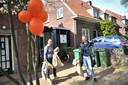 Secretaris Karin Janssen (links) van de Oranjevereniging Oosterbeek overhandigt Koningsdag-spelpakketten voor kinderen.