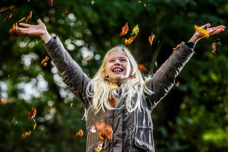 Dit meisje amuseert zich alvast met de vallende bladeren.