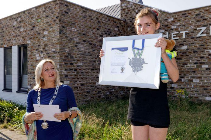 Quinty Verhoeven (rechts), leerling van Het Zilverlicht, loopt zeven km naar school om geld in te zamelen voor Wensambulance. De burgemeester reikt haar een kinderlintje uit.