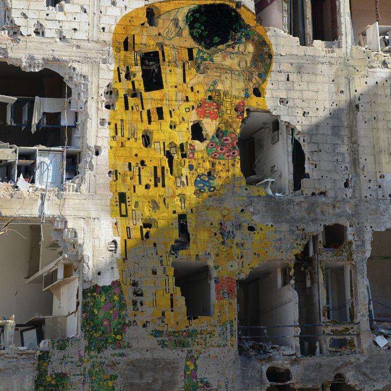 De Syrische graffiti-artiest Tammam Azzam plaatste - met Photoshop weliswaar - 'De kus' van Klimt op een volledig kapotgeschoten gebouw. Beeld rv