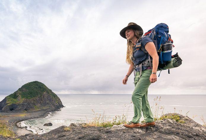 Een wandelaar in een afgelegen natuurgebied draagt aan het linkerschouder een satelliettracker van GeoDynamics