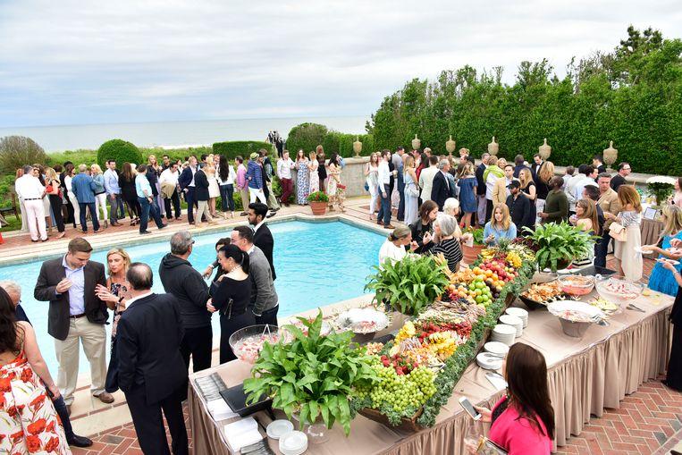 Een feestje in The Hamptons, waar de rich and famous graag hun zomer doorbrengen, maar nu al veel vroeger arriveren. Beeld Getty Images North America