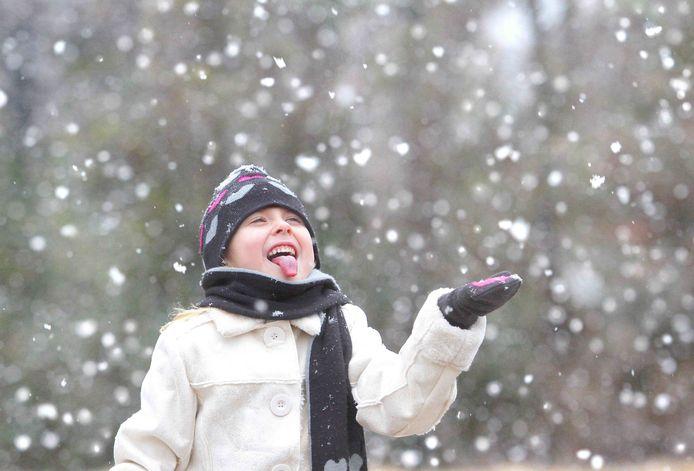 Een kind vangt sneeuwvlokken met haar tong.