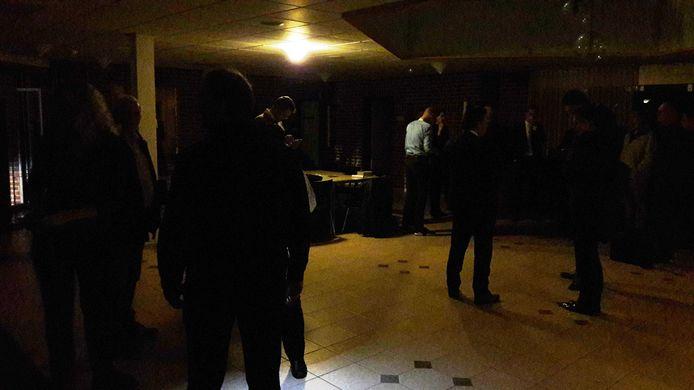 Raadsleden en publiek in de donkere hal van het gemeentehuis van Hasselt.