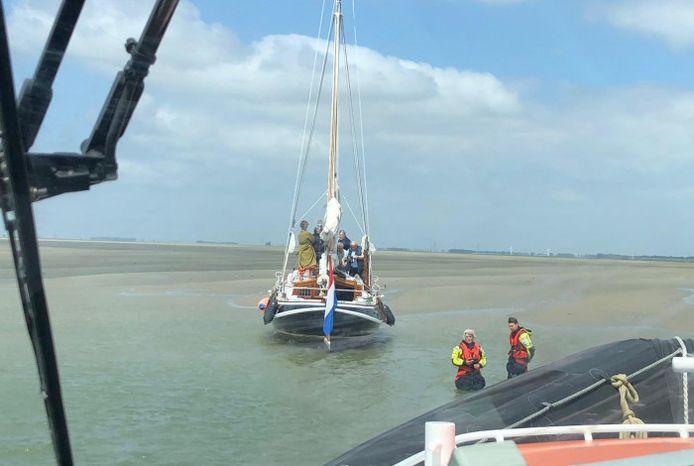 KNRM-leden staan in de Schaar van Ossenisse bij de zeilboot die met opzet was vastgelopen.