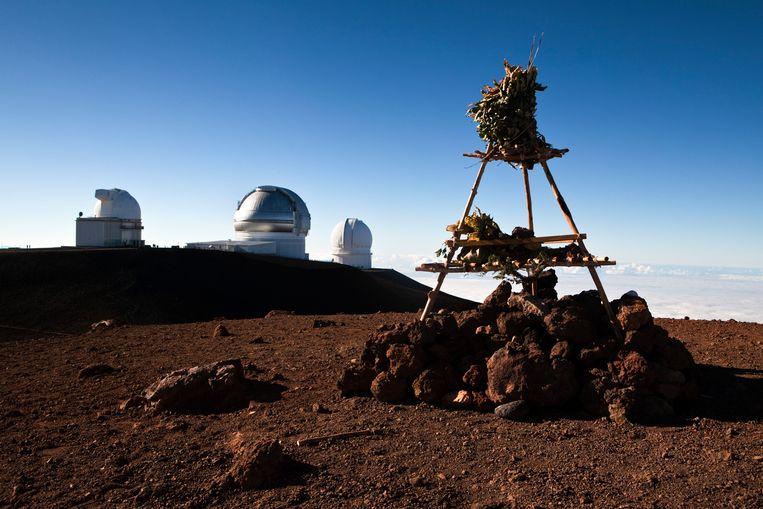 Tempel bovenop Mauna Kea, met op de achtergrond de telescopen van het huidige observatorium.  Beeld ullstein bild via Getty Images