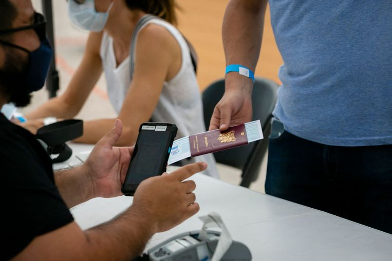 Een man in South Beach, Florida, meldt zich met paspoort bij een prikstraat. Beeld AFP