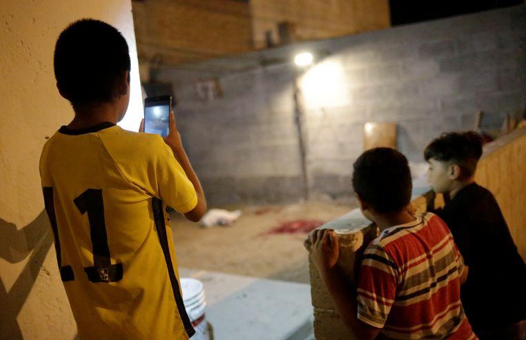 Kinderen kijken naar de plaats delict in Ciudad Juarez.  Beeld REUTERS