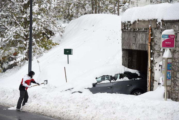 Een man probeert zijn auto te bevrijden uit de sneeuw in Firminy in de Haute Loire in Frankrijk.