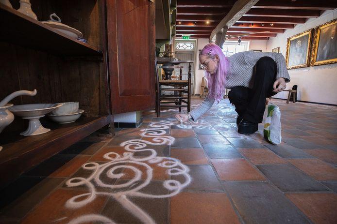 Esmee Teeuw maakt zandkunst op de vloer van 't Oude Slot in Veldhoven.