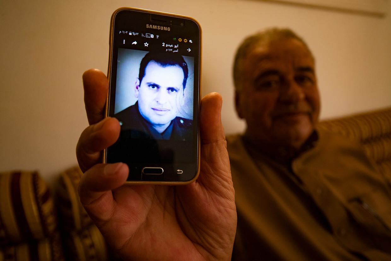Hassan al Jado'a thuis in Raqqa met het portret van zijn broer kolonel Abdallah.  Beeld Delil Souleiman