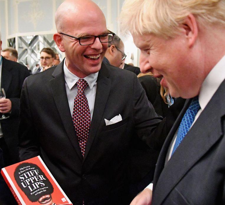 Brits minister Boris Johnson (rechts) neemt het boek van Harry De Paepe in ontvangst in Manchester.