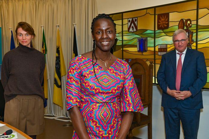 Sabelle Diatta, samen met gemeenteraadsvoorzitster Charlotte Castelein en burgemeester Marc Vanden Bussche.