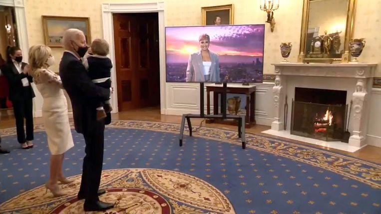 Jill en Joe Biden kijken in het witte huis naar de livestream Celebrating America. De president met kleinzoon op de arm.  Beeld Getty Images