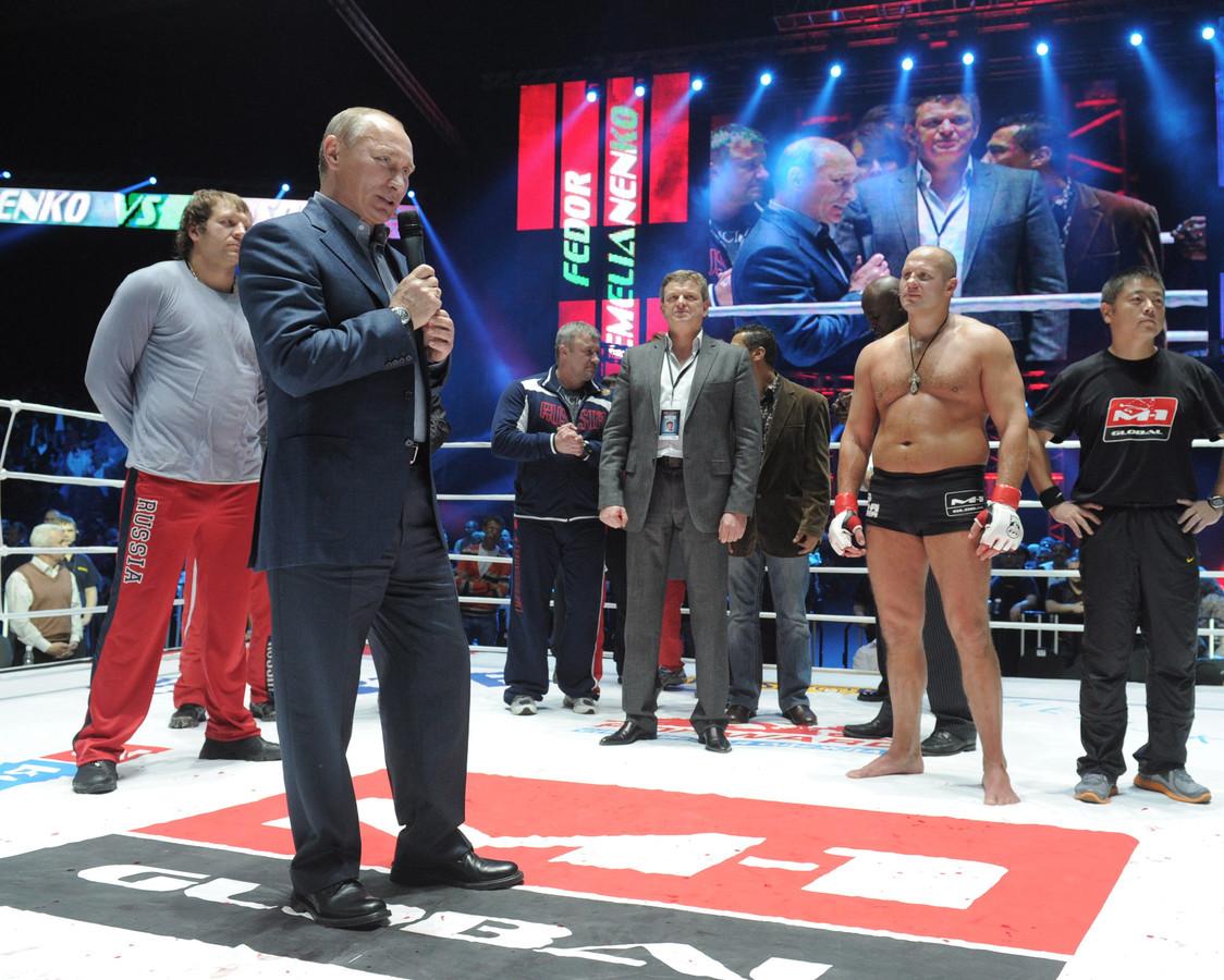 Vladimir Poetin feliciteert de Russische Fedor Emelianenko (tweede van rechts)  met zijn overwinning op Jeff Monson tijdens de M-1 Global mixed-fight show in Moskou, Rusland , 20 november 2011.