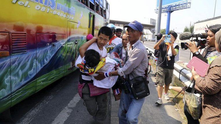 Demonstranten dragen een gewonde kameraad in Bangkok vandaag. Beeld reuters