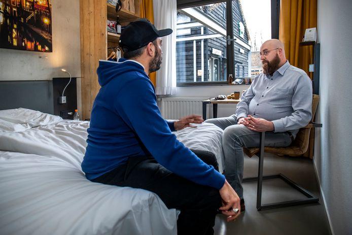 Hotelmanager Floris van Es in gesprek met een van de daklozen die in Star Lodge wordt opgevangen.