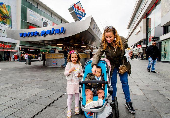 Een gezin doet zich op het Binnenwegplein in Rotterdam tegoed aan de frites van de patatkoning.
