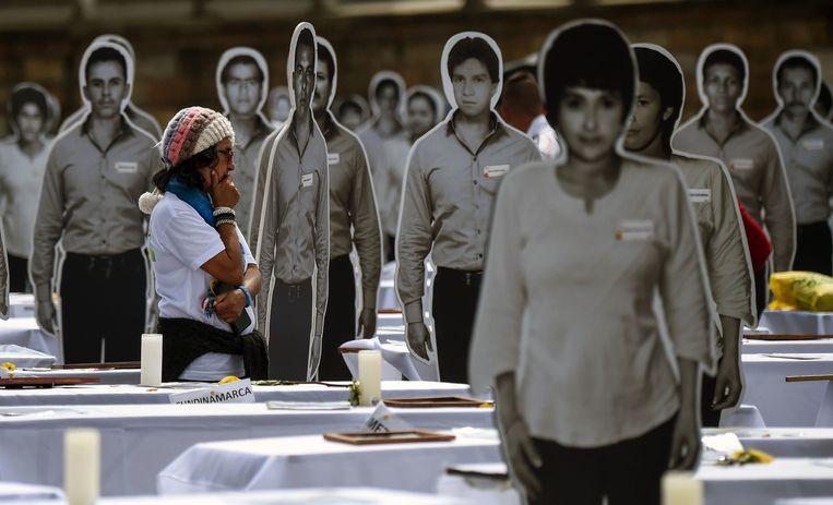 Een vrouw op het Bolivarplein in Bogota loopt tussen afbeeldingen op waar formaat van vermisten van de Patriotic Union, de partij die was gelieerd aan de Farc. Beeld AFP