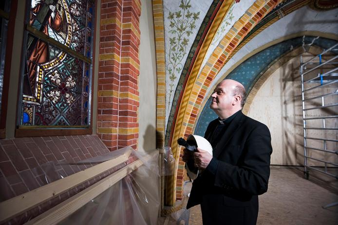 Bisschop Hans van de Hende bekijkt hoog boven de grond een detail van een van de gebrandschilderde ramen van de Sint Franciscuskerk die momenteel wordt gerestaureerd