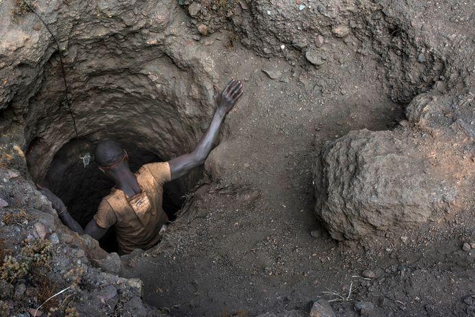 Een mijnwerker daalt af in een schacht van een kobaltmijn in Congo.