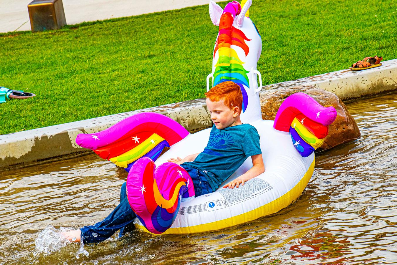 Een jongetje speelt in het Spoorpark in het water tijdens de roodharigen dag.