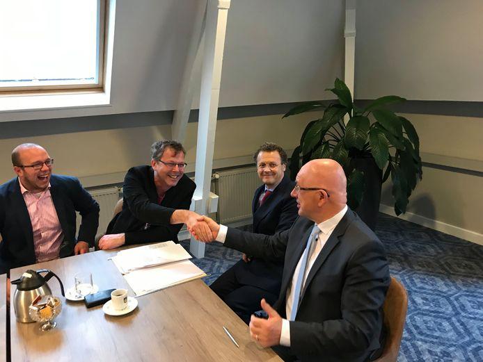 Burgemeester Pierre Bos(r) feliciteert Ad Vlems van het Ecodorp met de aankoop van de grond. Wouter Harperink (l) en notaris  Ties van Gulick kijken toe