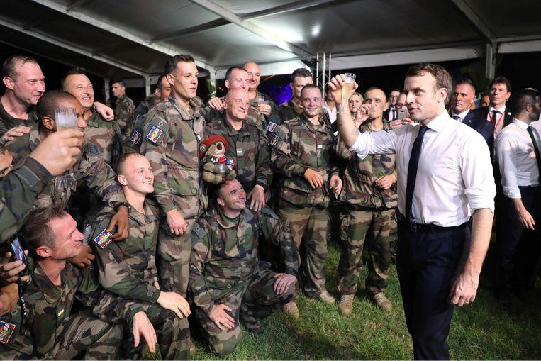 De Franse president Emmanuel Macron viert zijn verjaardag met Franse soldaten tijdens een kerstdiner in een militair kamp bij Abidjan in Ivoorkust.   Beeld AFP