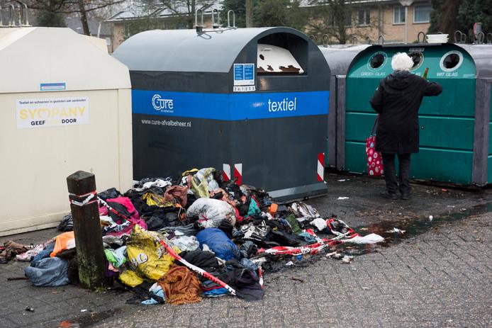 Een afgebrande kledingcontainer door ingeworpen vuurwerk op de Orionstraat in Eindhoven. De door de brandweer verwijderde en gebluste kledingstukken liggen er nog voor.