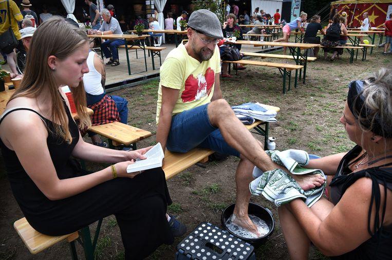 Festival Bezoekers hebben de mogelijkheid hun voeten te laten wassen om het idee terug te halen vanuit de bijbel zoals Jezus dat deed. Beeld Marcel van den Bergh